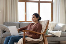 Cute Thing. Laughing Millennial Mixed Race Female User Read Funny Message In Dating Web Chat On Laptop Screen Enjoy Joke Of Day On Humorous Website. Smiling Indian Woman Enjoy Weekend At Home By Pc
