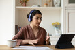 Leinwandbild Motiv Confident young biracial female freelance specialist consult client from home by videocall using tablet pc headphones. Busy indian lady discuss terms conditions of documents meeting with lawyer online