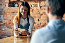 Female Waiter With A Cup Of Coffee Serves A Customer