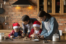 Smiling Family Couple With Happy Small Kids Wearing Aprons, Decorating Gingerbread Christmas Cookies Standing At Table In Modern Kitchen, Preparing For New Year Winter Holidays Celebration Together.