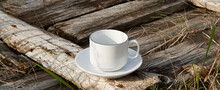 A White Cup Stands Empty On An Old Wooden Table. A White Cup On A Saucer Stands On An Old Wooden Table.