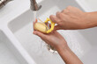 Woman peeling potato over kitchen sink with garbage disposal at home, closeup