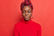 Portrait Of Serious Dark Skinned Woman Looks Directly At Camera With Calm Self Confident Expression Poses For Making Photo Dressed In Casual Poloneck Silk Scarf Wrapped On Head Isolated On Red