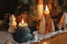 Christmas Advent. Stylish Burning Christmas Candles, Pine Trees And Cones Modern Decorations On Rustic Old Wooden Background In Evening Scandinavian Room. Atmospheric Moment