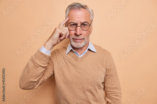 Fotografia Serious mature bearded man keeps finger on temple tries to recall something in mind focused at camera wears spectacles casual jumper isolated over brown background