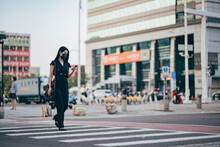 Young Asian Woman With Protective Face Mask Using Smartphone On The Go, Against Illuminated Neon Commercial Signs In City Street In Downtown District At Night.