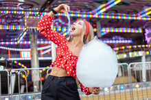 Adorable Cute Beautiful Woman With Cotton Candy Stands In The Middle Of An Amusement Park With Bright Colors, Positive And Cheerful, Happy And Optimistic Emotion