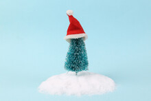 Christmas Tree With Santa Hat In Snowdrift On A Turquoise Background. Minimal Layout