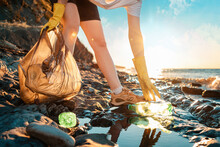 Cleaning The Coastal Zone. An Activist Picks Up A Plastic Bottle On The Beach. Close Up Of Hands. In The Background, The Sea And The Sunset. Bottom View