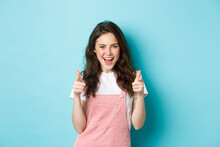 Confident And Cheerful Brunette Girl Say Yes, Pointing Fingers At Camera And Looking Sassy, Praising You, Inviting To Event, Standing Over Blue Background