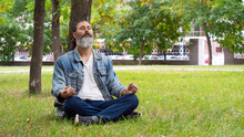Photo Of A Bearded Middle-aged Man Taking A Break From The Hustle And Bustle Of The City. He Is Meditating In The Park Under A Tree. Digital Detox Concept. Format Photo 16x9.