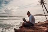 Fototapeta Fototapety z morzem do Twojej sypialni - Cyfrowy nomada, człowiek pracujący z laptopem i smartfonem zdalnie na tle oceanu i skał siedzący na wybrzeżu.
