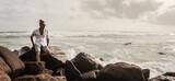 Fototapeta Fototapety z morzem do Twojej sypialni - Mężczyzna elegancko ubrany stojący na skałach na tle oceanu i wzburzonych fal.