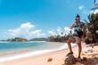 Mężczyzna z laptopem i telefonem na tle tropikalnego wybrzeża