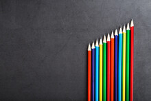 A Set Of Colorful Pencils On A Textured Dark Background