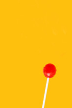 Red Lollipop Isolated On A Yellow Background