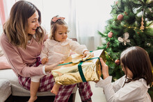 Happy Mother With Daughters And Gift Box On Christmas Day