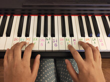Hands Of A Person Playing Piano, Piano Learning Concept, Reminder Notes With Note Papers On Piano Keys