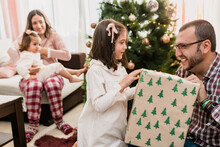 Smiling Father Passing Gift Box To Daughter On Christmas Day