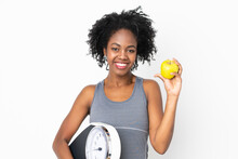 Young African American Woman Isolated On White Background With Weighing Machine And With An Apple