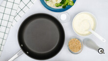 Cauliflower And Broccoli Casserole Recipe. Frying Pan, Vegetables, Alfredo Sauce, And Bread Crumbs Close Up On Kitchen Table, Flat Lay