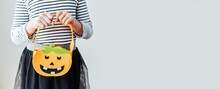 A Girl Dressed As A Witch Holds A Felt Basket In Her Hands For Collecting Sweets For The Halloween Holiday. Banner. Place For Text