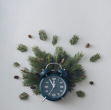 Alarm Clock And Pine Branches On A Gray Background Concept Of Winter Holidays And Vacations Flat Lay