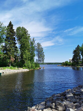 The Strait Of Vyborg Bay Between The Island With A Grotto And The Peninsula With The Temple Of Neptune In The Rocky Natural Park Monrepos Of The City Of Vyborg On A Clear Summer Day.