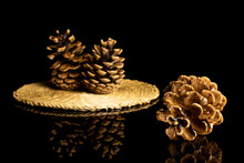 Group Of Three Whole Beautiful Pine Cone On Straw Coaster Isolated On Black Glass