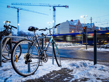 Old Bicycle Parked On A Rack In A Winter City, Urban Environment With Construction Site On Background