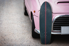 Old Surfskate With Pink Vintage Car On Road In The Parking.