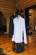 Groom's Wedding Accessories. White Shirt, Jacket, Leather Belt Hang On Wooden Bear Sculpture And Interior In The Morning.