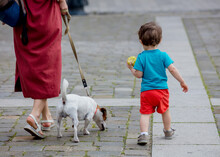 Little Toddler Boy And Mother With A Dog In The Old Town