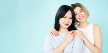 Ethnic Diversity. Friendly Women. International Tolerance. Conceptual Banner. Happy Asian Caucasian Ladies Embracing Each Other Isolated Blue Copy Space Wide Ledge.