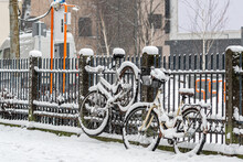 Snow Covered Bicycles Are Parked On The Sidewalk Against A Fence In Wintry City