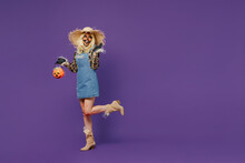 Full Body Side View Young Woman With Halloween Makeup Mask Wearing Straw Hat Scarecrow Costume Hold Jack-o'-lantern Pumpkin Isolated On Plain Dark Purple Background Studio Celebration Holiday Concept.