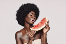 Portrait Of Beautiful Young African Woman Holding Slice Of Watermelon And Smiling