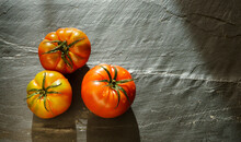 Still Life With Three Organically Grown Tomatoes On A Dark Background With Copy Space To The Right Of The Image.