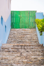 Grey Stairs And Blue Historical Buildings With Green Wooden Doors