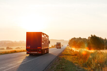 Arriving Truck On The Road In A Rural Landscape At Sunset