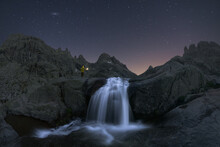 Tourist Contemplating Waterfall On Mountain Under Stars At Night