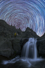 Tourist Contemplating Waterfall On Mountain Under Star Trail At Night