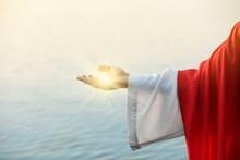 Jesus Christ Near Water Outdoors, Closeup. Miraculous Light In Hand