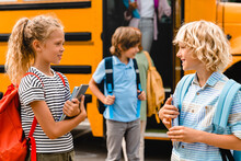 Two Small Classmates Schoolchildren Pupils Talking Discussing Communicating With Each Other At The School Yard Getting Off The School Bus, Going Back To Classes Lessons After Summer Holidays Lockdown.