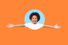 Let's Hug. Portrait Of Friendly Little Boy With Curls In White T-shirt Smiling Happily And Holding Hands Wide Open To Embrace, Welcome. Indoor Shot Isolated In A Round Hole On Orange Background