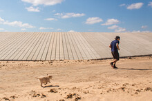 Young Boy Trotting With His Puppy In The Sand.