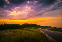 Dramatic Cloudscape With Glowing Sun Rays Over The Coastal Road With Wild Plants At Sunrise