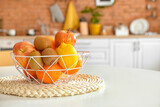 Basket with tropical fruits on table in kitchen