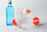 Glass of cold gin tonic and grapefruit slices on light background