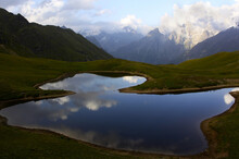 Mesmerizing View Of A Reflective Pond On The Background Of The Mountains Under A Cloudy Sky